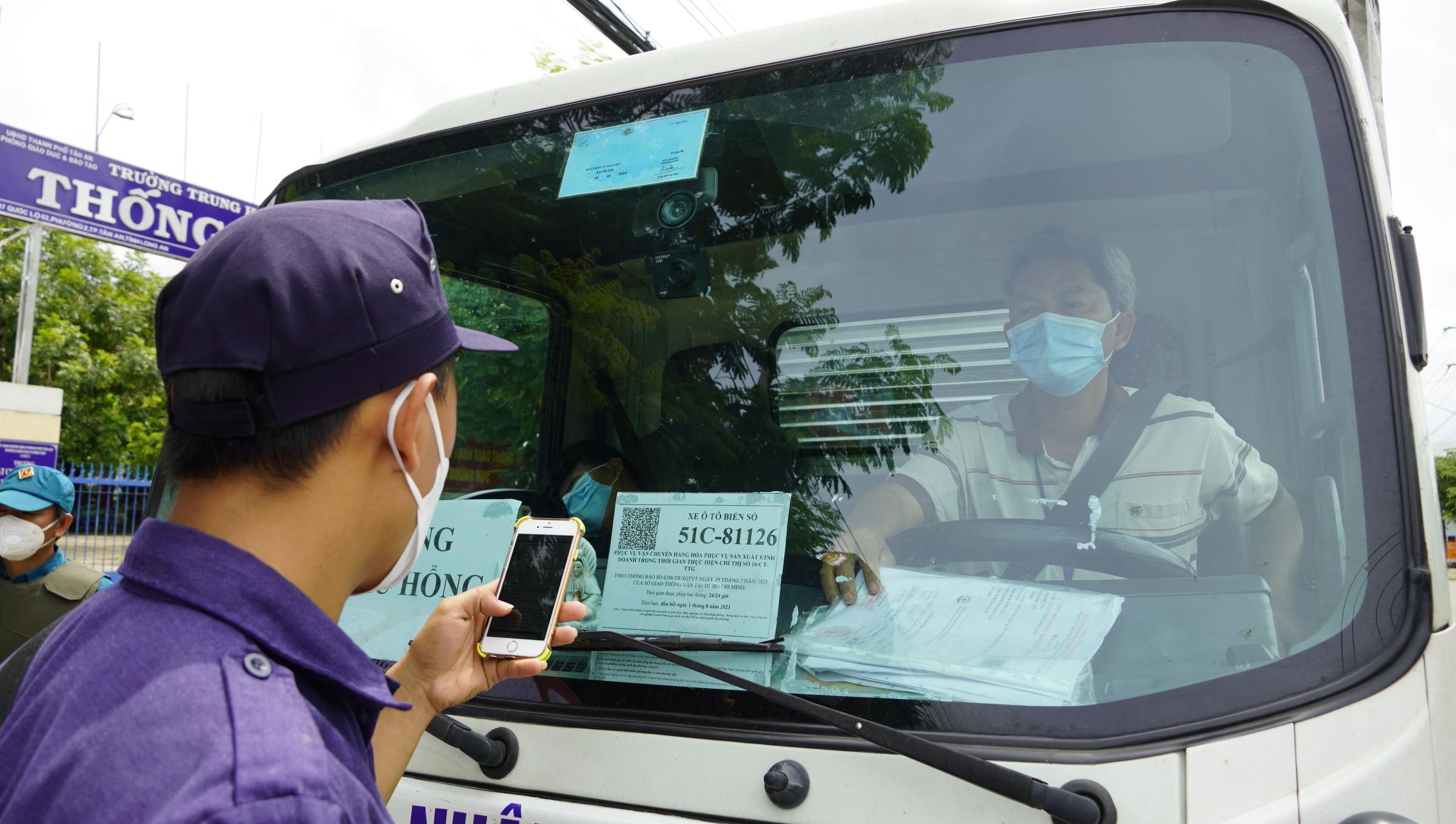 Lực lượng dân phòng dùng điện thoại quét mã QR luồng xanh trên một xe tải tại chốt kiểm soát quốc lộ 62, phường 2, TP Tân An, Long An. Ảnh: Hoàng Nam