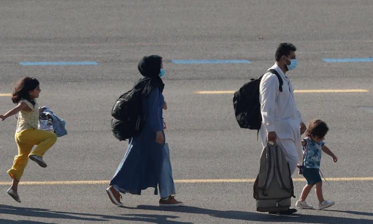 Bé gái Afghanistan nhảy chân sáo trên đường băng của sân bay quân sự Melsbroek, Bỉ, hôm 25/8. Ảnh: Reuters.