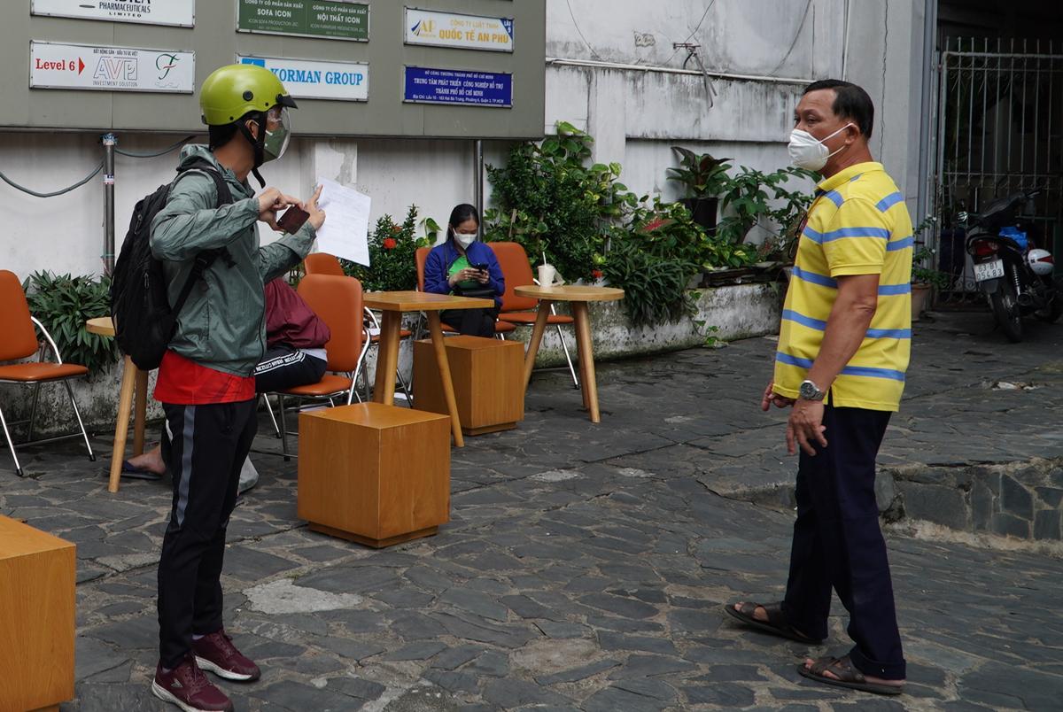Một đại diện doanh nghiệp hỏi thông tin ghi phiếu chờ làm thủ tục cấp giấy đi đường tại Sở Công thương TP HCM, trưa 27/8. Ảnh: Gia Minh