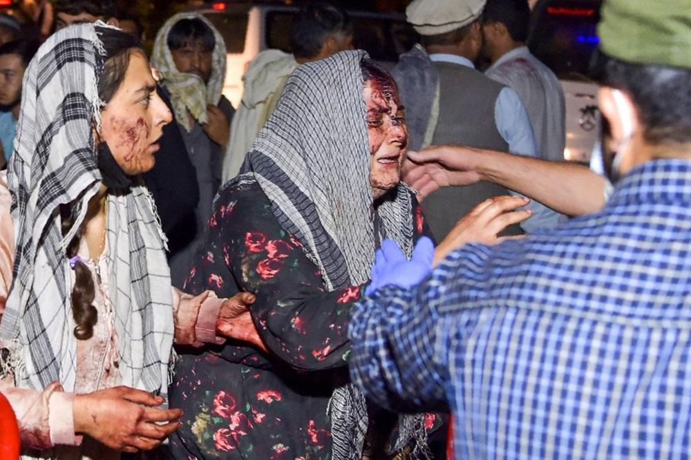Một phụ nữ bị thương đượ đưa đến bệnh viện điều trị sau hai vụ nổ bên ngoài sân bay Kabul hôm 26/8. Ảnh: AFP.