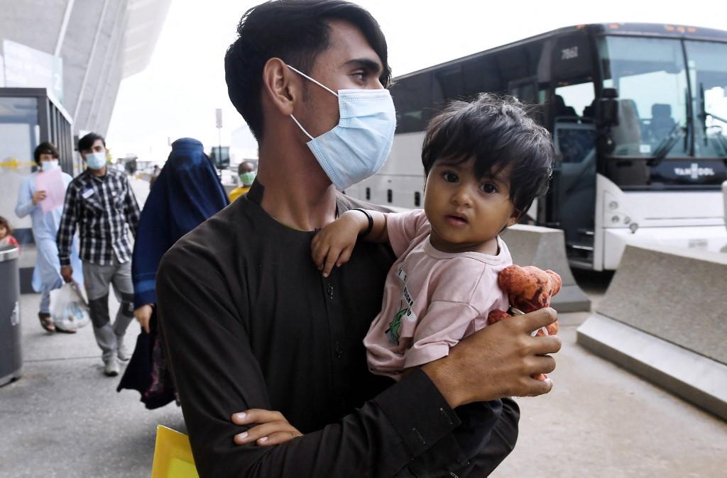 Người tị nạn Afghanistan lên xe buýt tại sân bay ở Dulles, Virginia ngày 27/8 sau khi được sơ tán khỏi Kabul. Ảnh: AFP