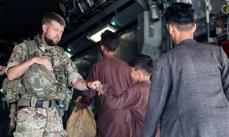 Binh sĩ Anh đấm tay với một cậu bé Afghanistan đang sơ tán khỏi sân bay Kabul. Ảnh: Reuters.