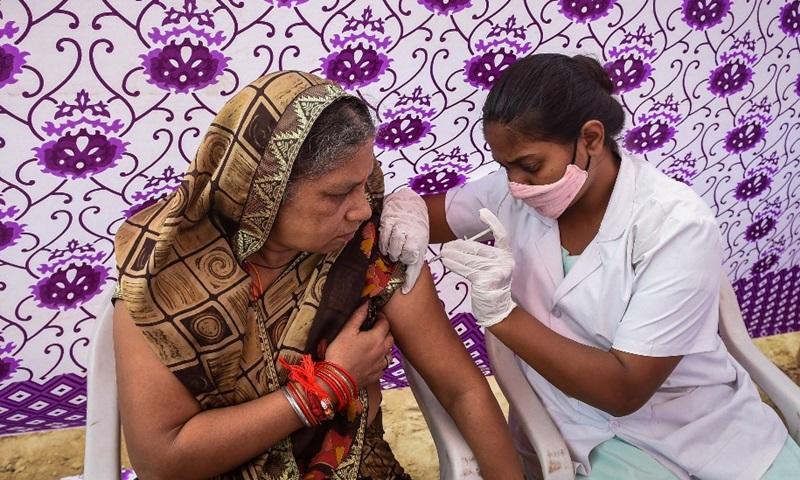 Nhân viên y tế tiêm vaccine Covid-19 cho một phụ nữ tại điểm tiêm chủng tạm thời ở thành phố Ahmedabad, bang Gujarat, Ấn Độ hôm 26/8. Ảnh: AFP.