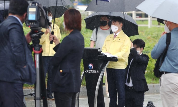 Nhân viên quỳ gối che ô cho Thứ trưởng Tư pháp Hàn Quốc Kang Sung Kook tại Jincheon, tỉnh Bắc Chungcheong, hôm 27/8. Ảnh: Yonhap.