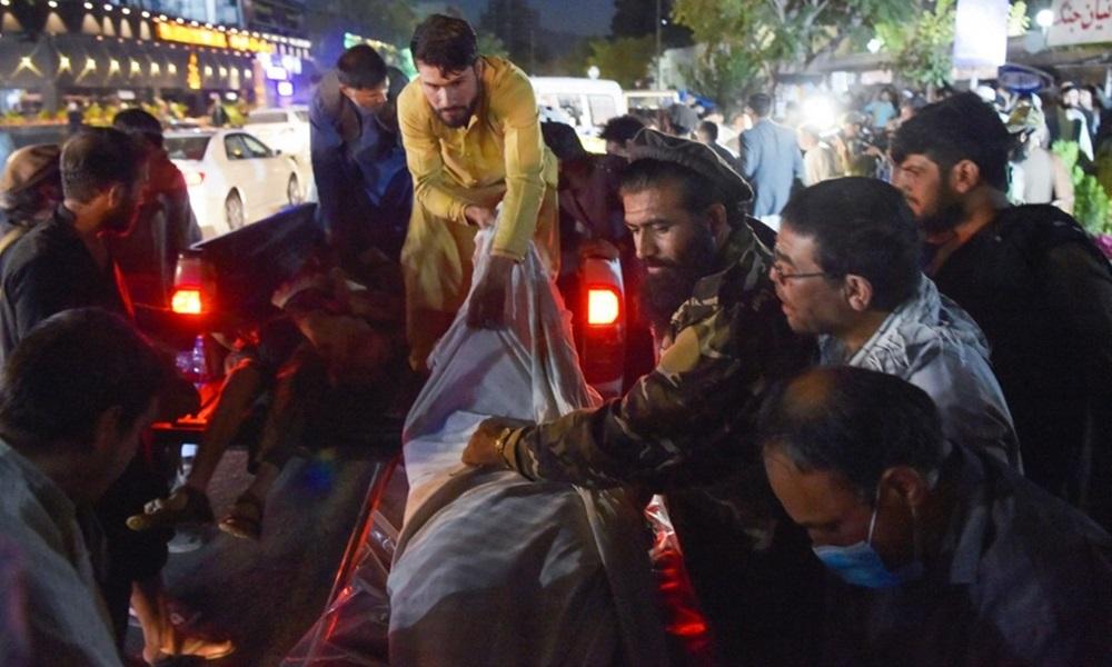 Nhân viên y tế và tình nguyện viên di chuyển thi thể một nạn nhân vụ đánh bom ở sân bay Kabul, Afghanistan hôm 26/8. Ảnh: AFP.