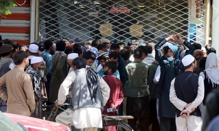 Người xếp hàng chờ rút tiền bên ngoài ngân hàng New Kabul Bank của Afghanistan ngày 28/8. Ảnh: AP.