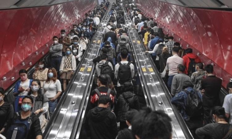 Người đi làm xếp hàng trên thang máy bên trong một ga tàu điện ngầm ở Quảng Đông, Trung Quốc. Ảnh: Reuters.