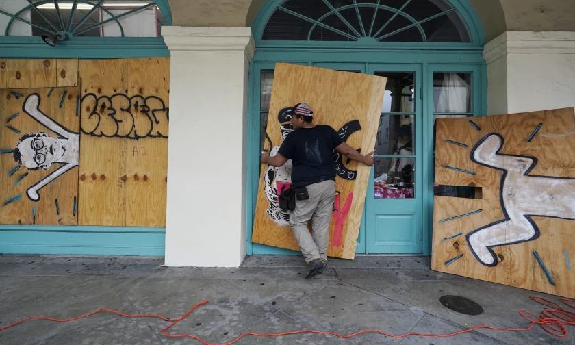 Nhân viên dùng ván gỗ gia cố cửa tiệm ở khu French Quarter, thành phố New Orleans hôm 28/8. Ảnh: AP.