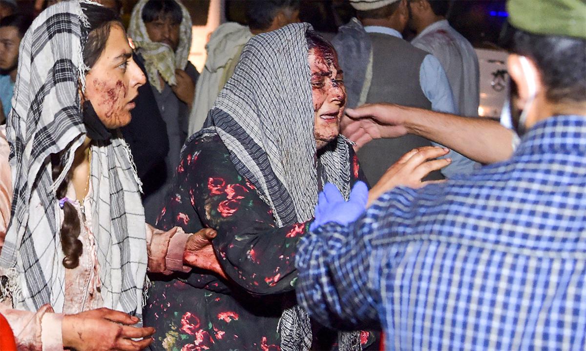 Hai phụ nữ Afghanistan bị thương trong vụ đánh bom ở sân bay Kabul ngày 26/8. Ảnh: AFP.