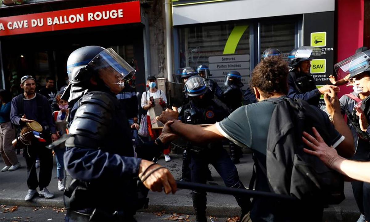 Cảnh sát chống bạo động Pháp vây quanh một người đàn ông tham gia biểu tình phản đối giấy thông hành Covid-19 ở Paris ngày 28/8. Ảnh: AFP.