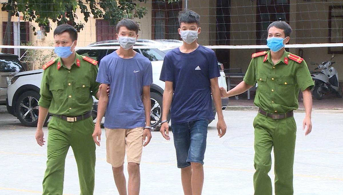 Hai nghi can Lê Văn Chiến (thứ hai từ phải sang) và Lê Văn Quyết bị cảnh sát bắt giữ. Ảnh: Lam Sơn.