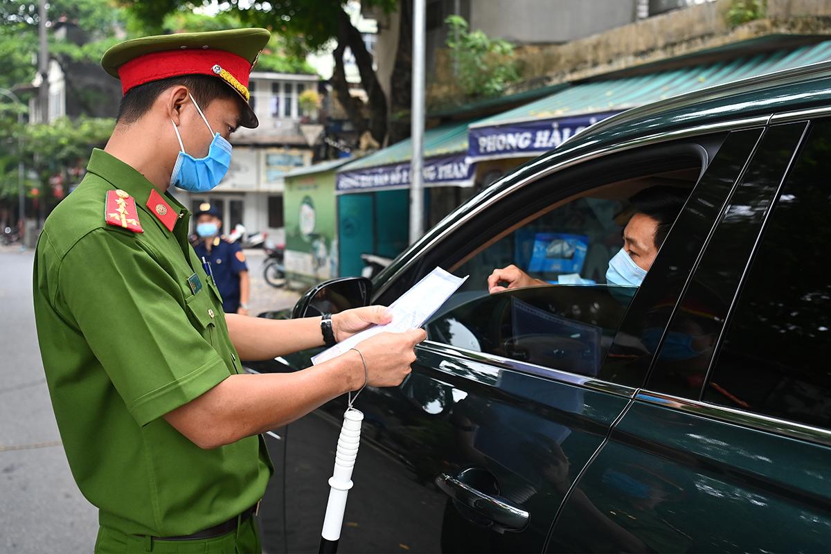 Cảnh sát kiểm tra giấy đi đường ở Hà Nội. Ảnh: Giang Huy.
