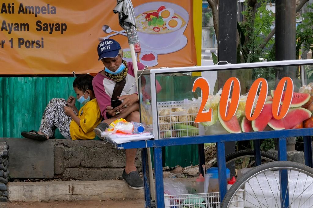 Một người bán hoa quả rong và con trai nghịch điện thoại di động trong lúc đợi khách ở Jakarta hôm 21/8. Ảnh: AFP