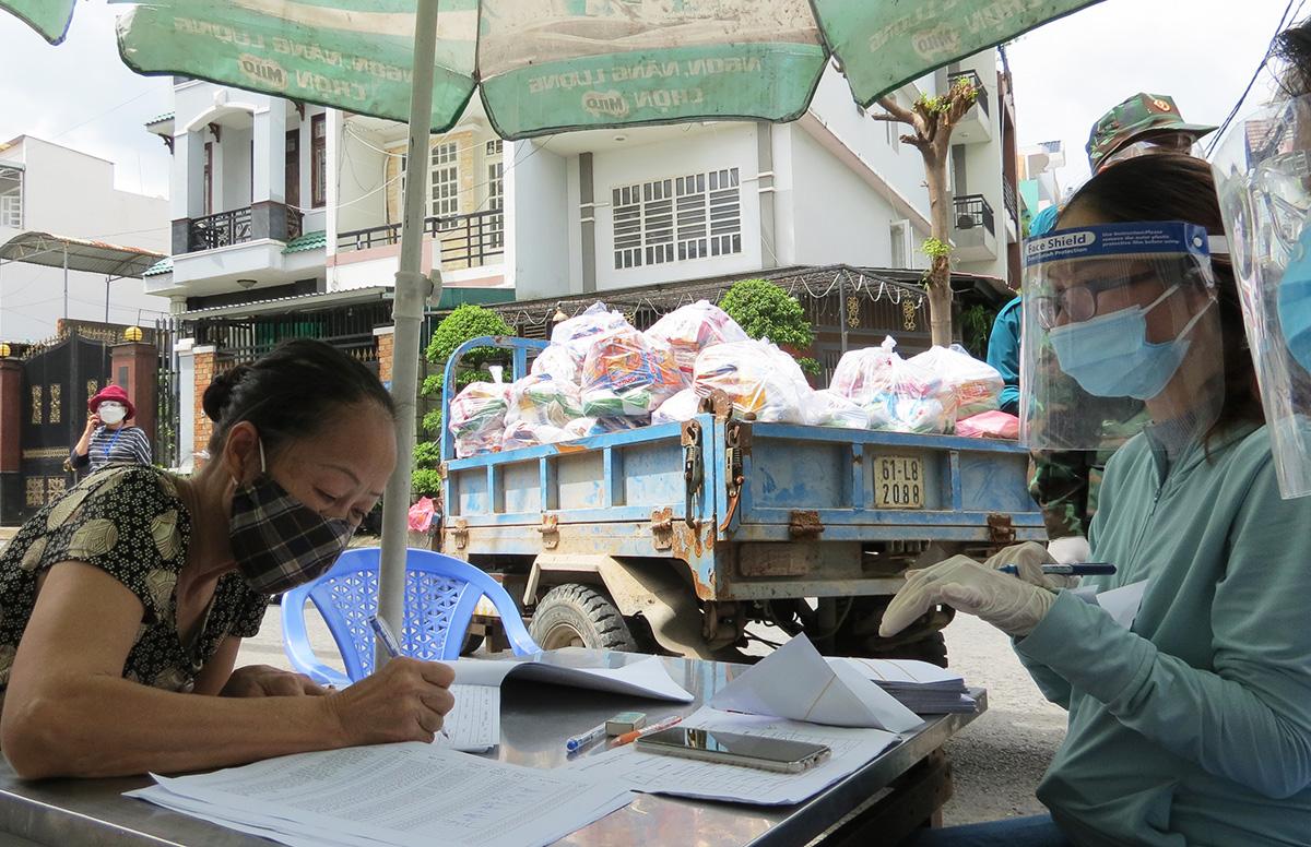 Người khó khăn ở phường 14 (quận Gò Vấp) nhận túi an sinh, tiền hỗ trợ từ chính quyền. Ảnh: Lê Tuyết