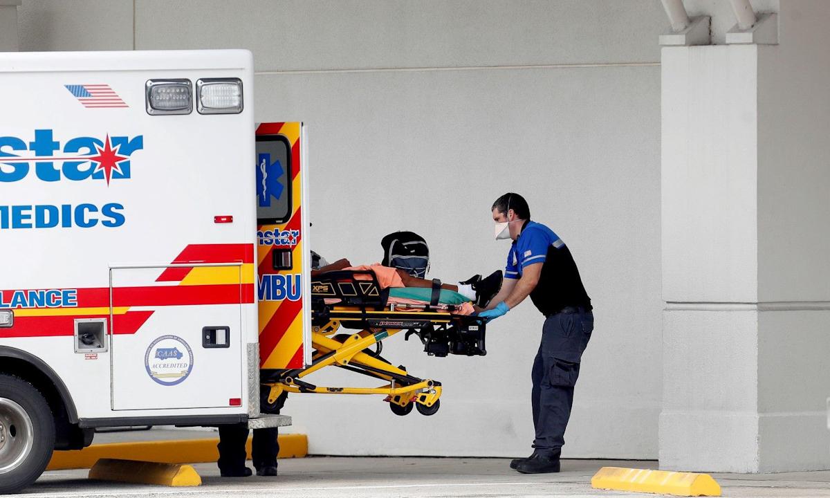 Nhân viên y tế chuyển người bệnh Covid-19 khỏi xe cứu thương ở bệnh viện Morton Plant, Clearwater, bang Florida hồi đầu tháng 8.