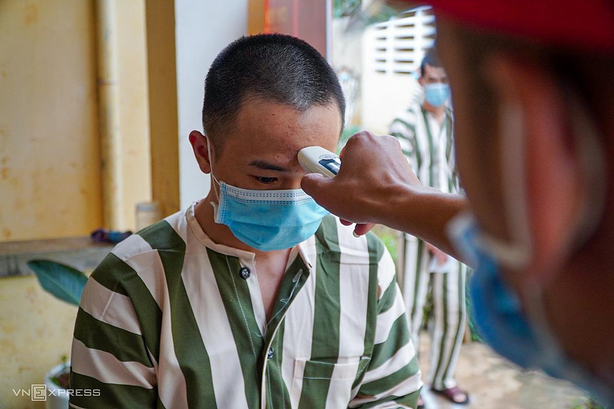 Một người ở trại tạm giam huyện Chư Păh, Gia Lai được đo nhiệt độ trước khi bỏ phiếu bầu cử ngày 23/5/2021. Ảnh: Trần Hoá