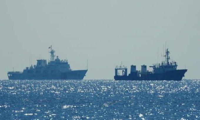 Tàu hải cảnh Trung Quốc (trái) đi gần một tàu không rõ quốc tịch trên Biển Đông ngày 14/4. Ảnh: Reuters.