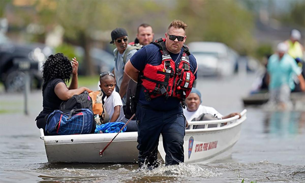 Nhân viên cứu hỏa bang Louisiana sơ tán người mắc kẹt vì lũ lụt do bão Ida gây ra tại thành phố New Orleans ngày 30/8. Ảnh: AP.
