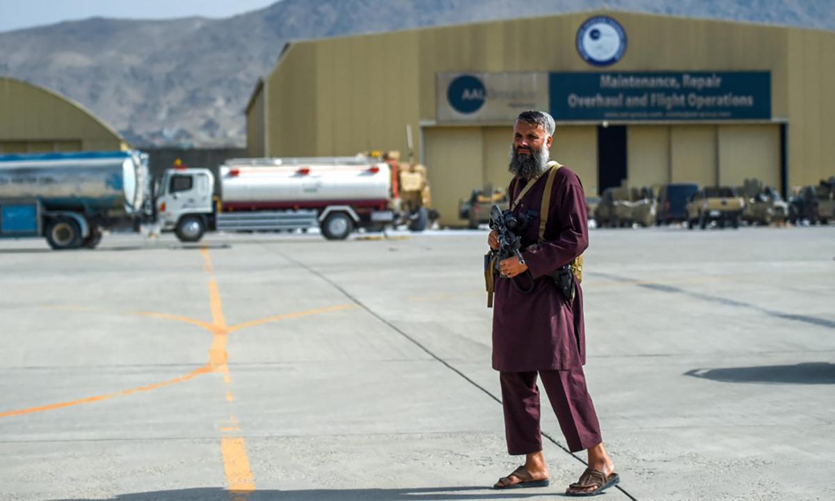 Một tay súng Taliban đứng trước xưởng bảo dưỡng và sửa chữa máy bay ở sân bay Kabul ngày 31/8. Ảnh: AFP.