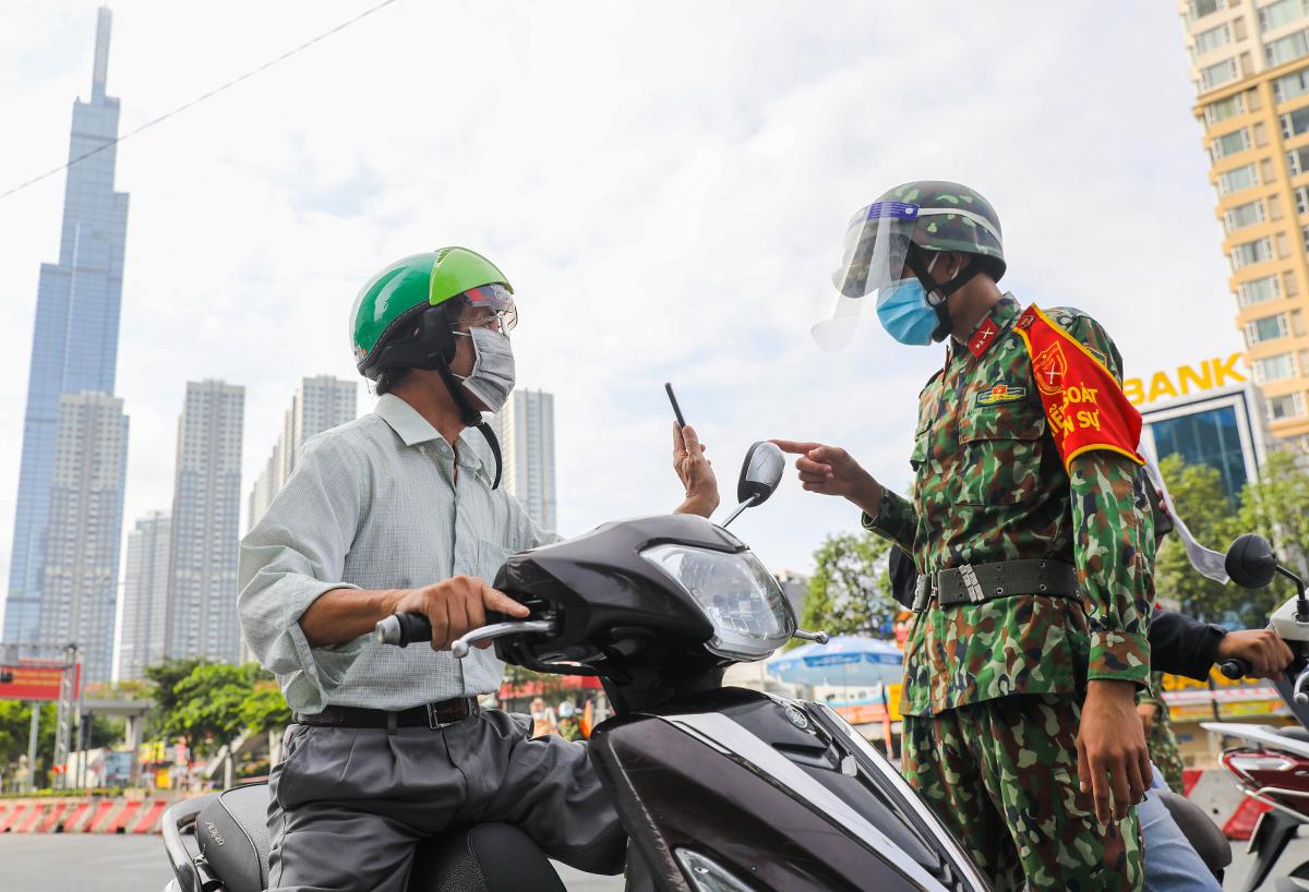 Người dân trình mã QR khi khai di chuyển nội địa tại chốt kiểm soát ở quận Bình Thạnh, ngày 30/8. Ảnh: Quỳnh Trần