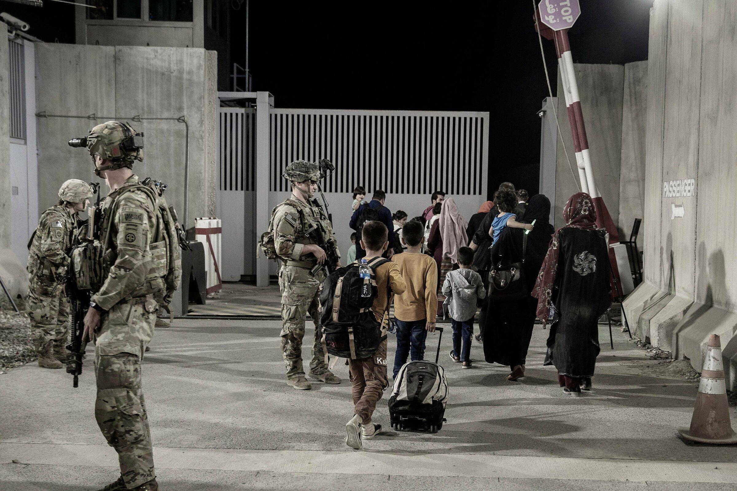 Lính thủy quân lục chiến Mỹ hướng dẫn người tị nạn qua cổng sân bay Kabul vào ngày 25/8. Ảnh: Bộ Quốc phòng Mỹ.