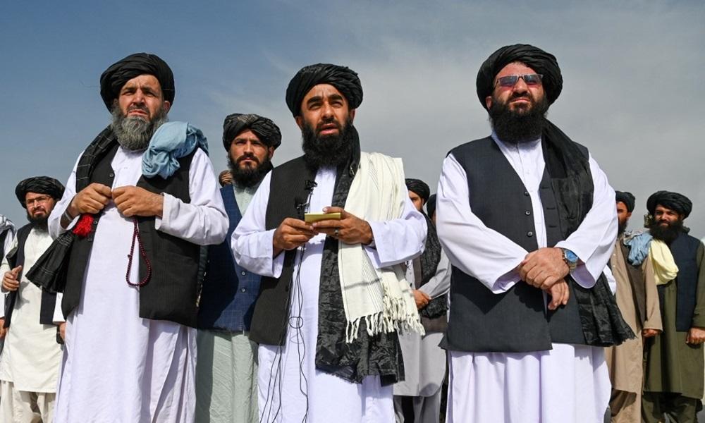 Phát ngôn viên Taliban Zabihullah Mujahid (giữa, hàng đầu) phát biểu với truyền thông tại sân bay Kabul, Afghanistan hôm nay. Ảnh: AFP.