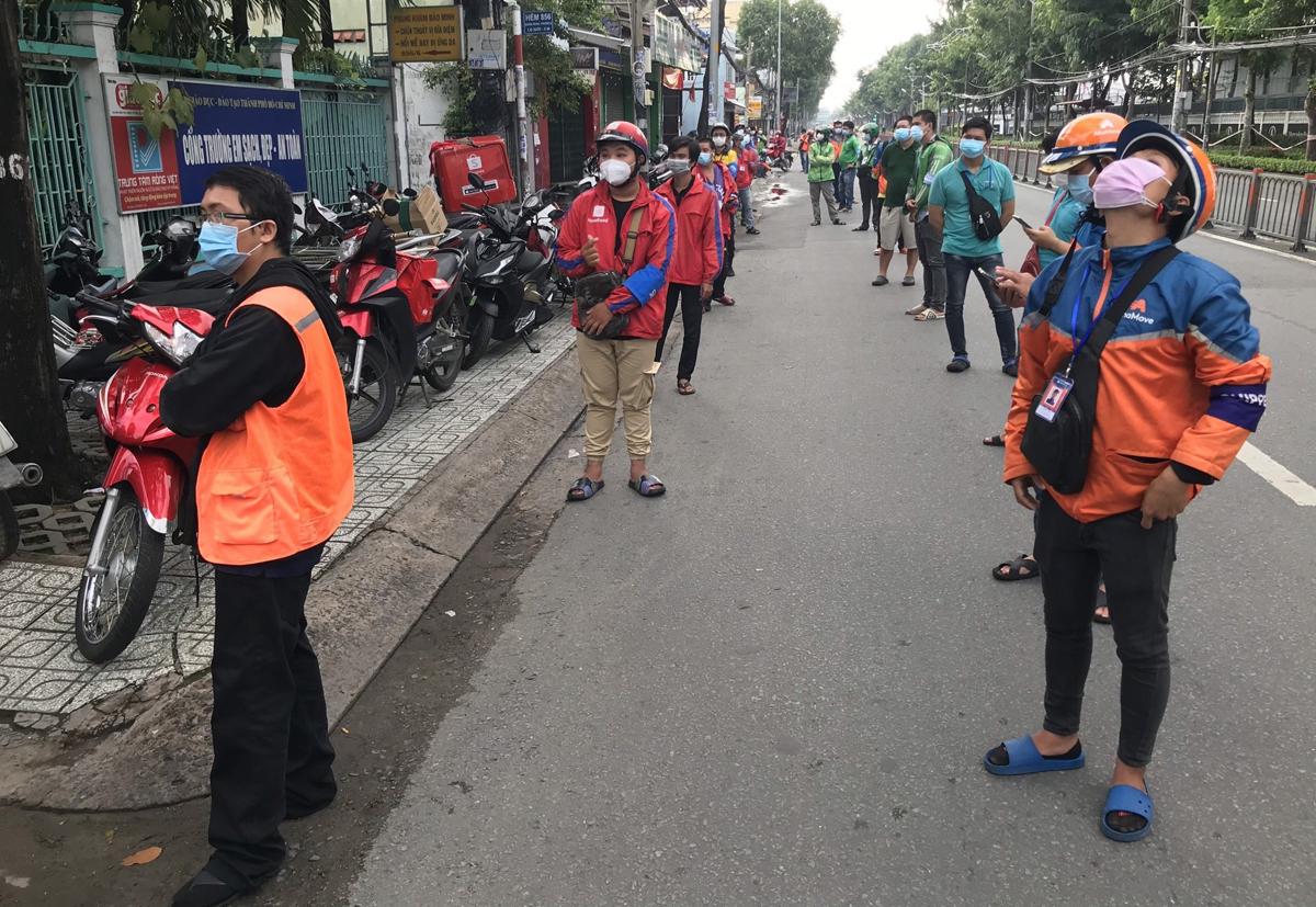 Shipper xếp hàng dài chờ lấy mẫu xét nghiệm nCoV tại trạm y tế lưu động ở đường Quang Trung, quận Gò Vấp, sáng 31/8. Ảnh: Đình Văn