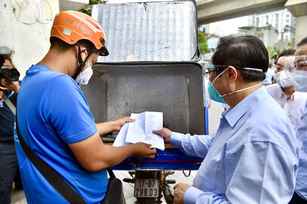 Thủ tướng Phạm Minh Chính kiểm tra giấy phép đi đường và khai báo y tế của một nhân viên giao hàng trên địa bàn quận Thanh Xuân, Hà Nội, chiều 31/8. Ảnh: Nhật Bắc