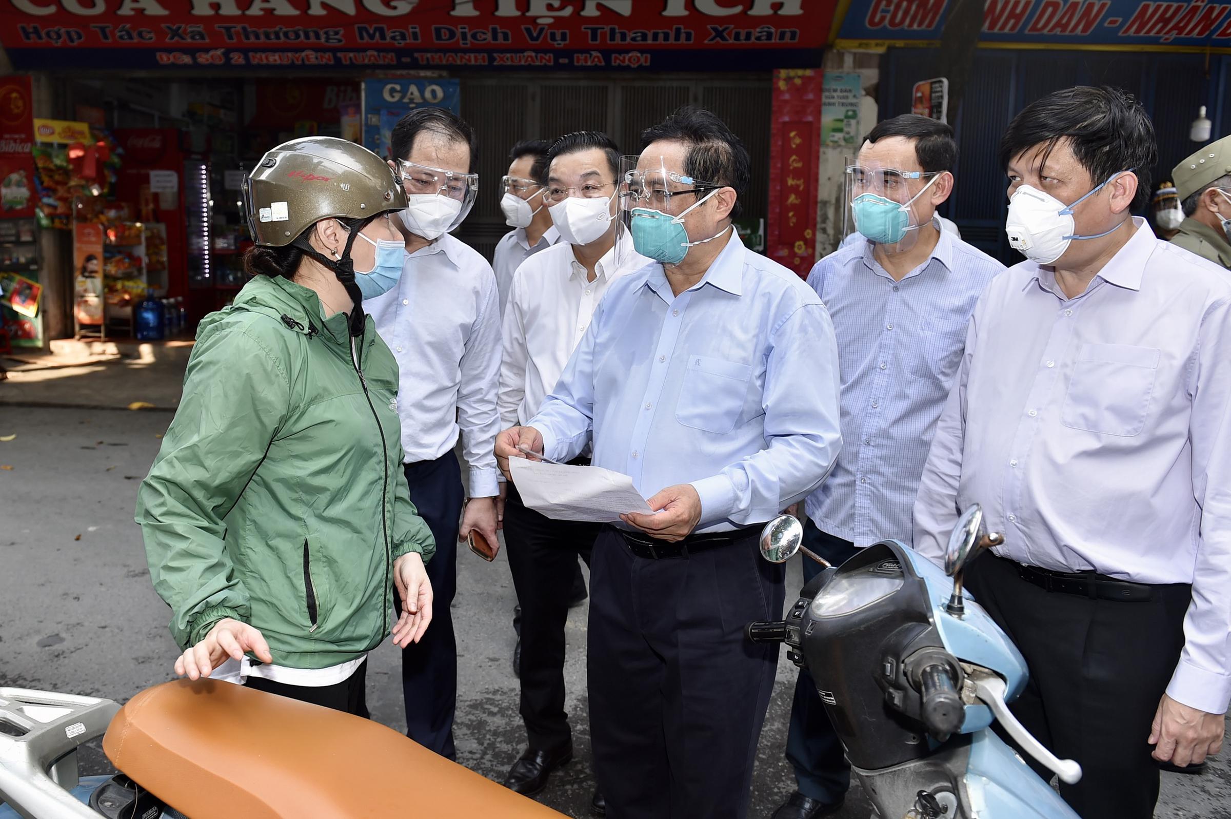 Thủ tướng Phạm Minh Chính kiểm tra giấy phép đi đường và khai báo y tế của người dân tại điểm chốt của công an phường Thanh Xuân Trung, Hà Nội, chiều 31/8. Ảnh: Nhật Bắc