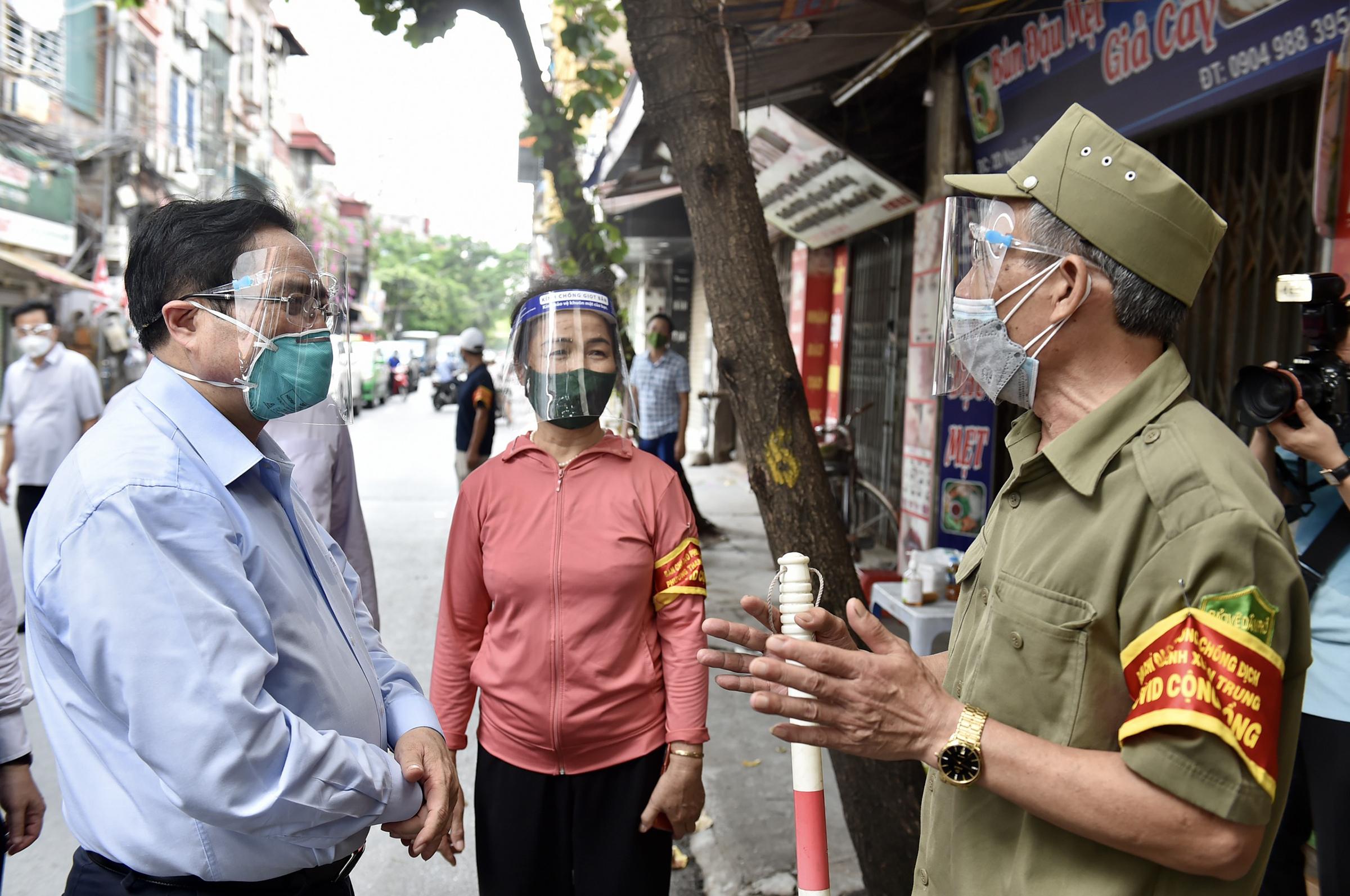 Thủ tướng hỏi thăm tình hình, động viên, chia sẻ với thành viên tổ Covid-19 cộng đồng đang thực hiện nhiệm vụ tại khu vực phường Thanh Xuân Trung, Hà Nội, chiều 31/8. Ảnh: Nhật Bắc
