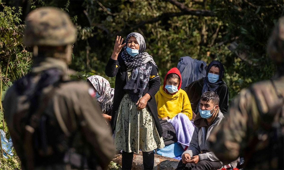 Một phụ nữ đứng trước nhóm người được cho là di dân Afghanistan cố gắng nói chuyện với biên phòng Ba Lan tại khu vực biên giới gần làng Usnarz Gorny ngày 20/8. Ảnh: AFP.