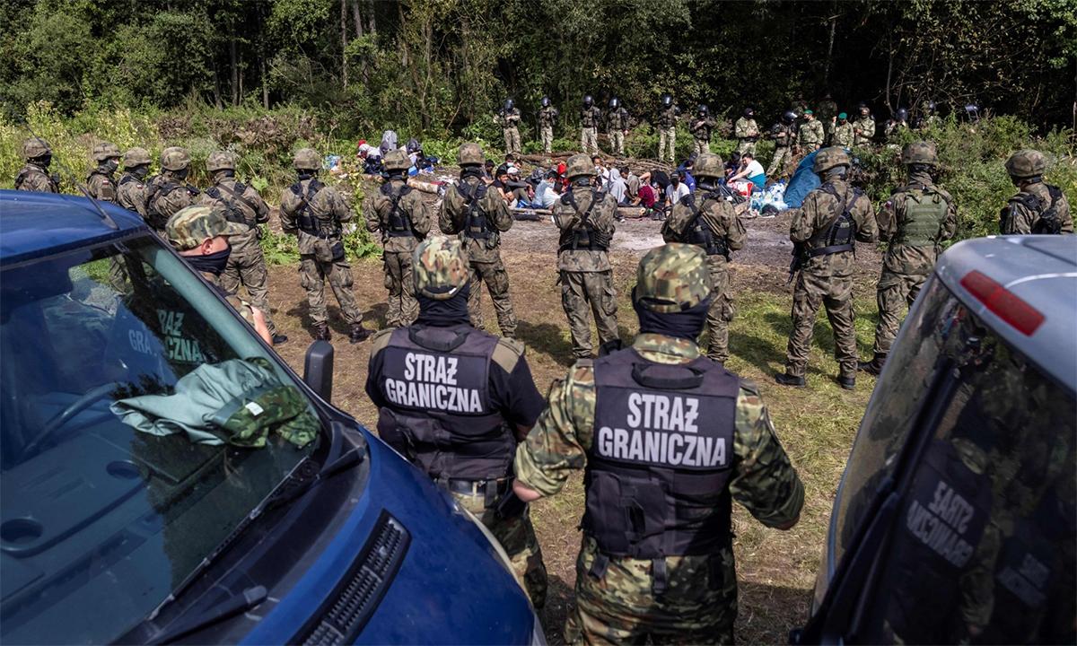Biên phòng Ba Lan đứng trước nhóm di dân được cho tới từ Afghanistan gần làng Usnarz Gorny ngày 20/8. Ảnh: AFP.