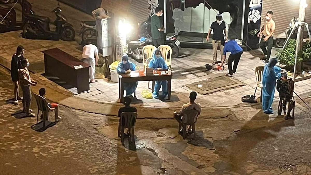 Cơ quan y tế lấy mẫu xét nghiệm cho người tiếp xúc gần ca dương tính ở phường Ngọc Trạo đêm 31/8. Ảnh: Lam Sơn.
