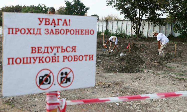 Nhóm khai quật đào bới các hố chôn cất ở thành phố Odessa, Ukraine. Ảnh: AFP