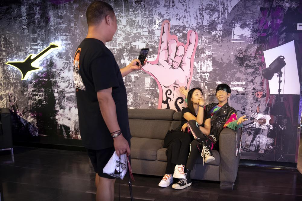 Khách thăm bảo tàng tượng sáp Madame Tussaud ở Bắc Kinh vào ngày 31/8 chụp ảnh cùng mô hình ca sĩ Thái Trương Vĩ. Ảnh: AP.