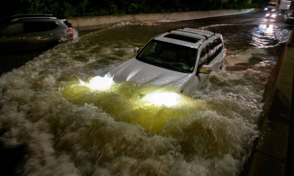 Một người lái xe ô tô qua đường cao tốc ngập nước ở Brooklyn, New York rạng sáng 2/9. Ảnh: AFP