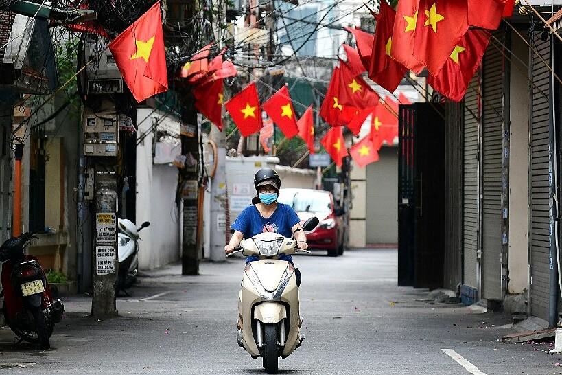 Một phụ nữ lái xe máy trong con hẻm treo đầy cờ tổ quốc mừng ngày Quốc khánh tại Hà Nội hôm 1/9. Ảnh: AFP