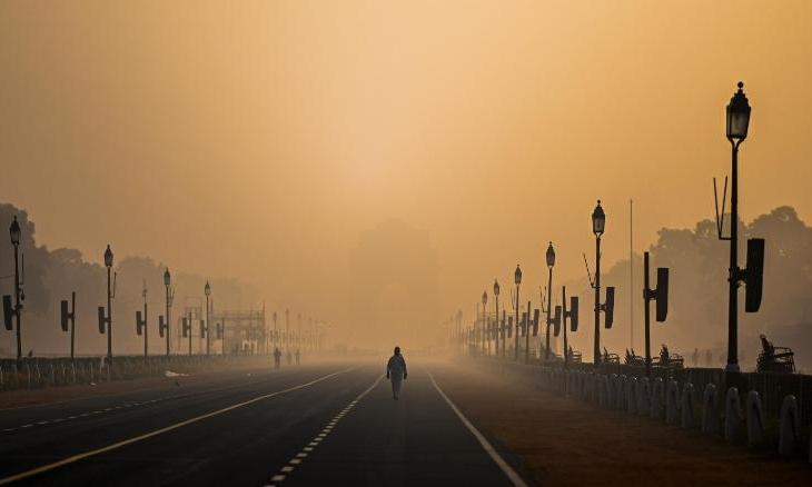 Một người đan ông đi bộ trong khói mù ở New Delhi, Ấn Độ, hôm 28/1. Ảnh: AFP