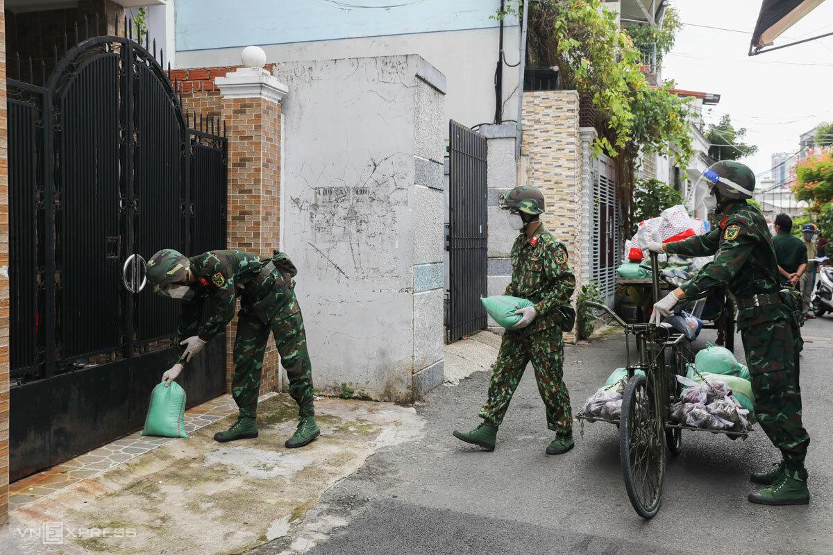 Bộ đội dùng xe đạp thồ chuyển hàng trăm kg gạo tiếp tế cho người dân trong hẻm sâu ở quận Bình Thạnh, TP HCM, ngày 2/9. Ảnh: Như Quỳnh
