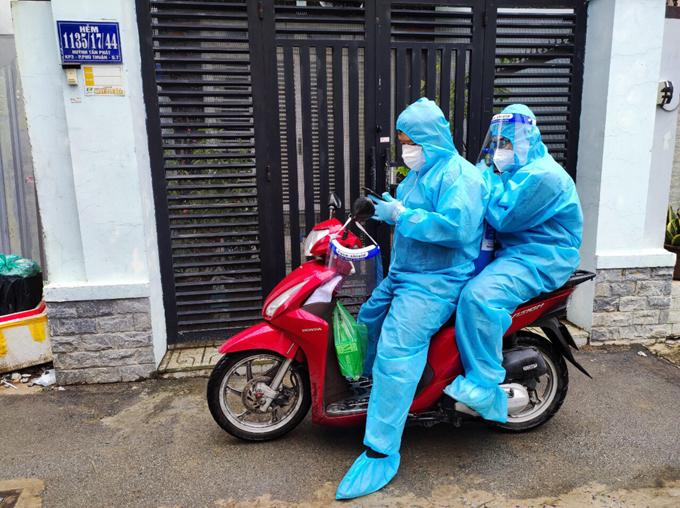 Anh Phát (ngồi trước) và Nhân tới hỗ trợ một bệnh nhân lớn tuổi ở hẻm Huỳnh Tuấn Phát, quận 7, hôm 11/8. Ảnh: Nhân vật cung cấp