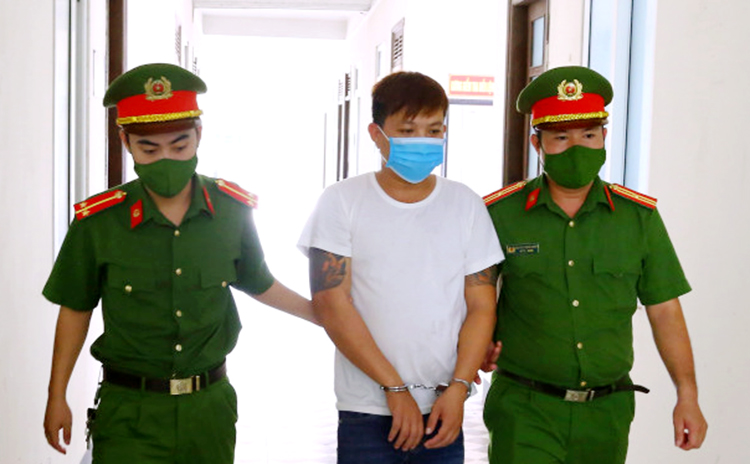 Điệp (áo trắng) bị cảnh sát dẫn giải về trụ sở lấy lời khai. Ảnh: Công an cung cấp