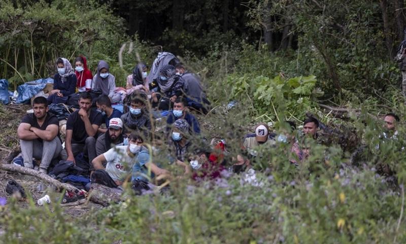 Người di cư được cho là đến từ Afghanistan ngồi trên mặt đất tại một ngôi làng gần Bialystok, đông bắc Ba Lan hôm 20/8. Ảnh: AFP.