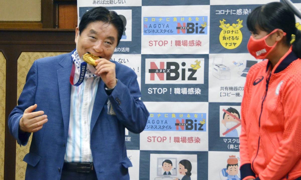 Thị trưởng Takashi Kawamura cắn huy chương vàng Olympic của tuyển thủ bóng mềm nữ Miu Goto tại tòa thị chính Nagoya hôm 4/8. Ảnh: Kyodo