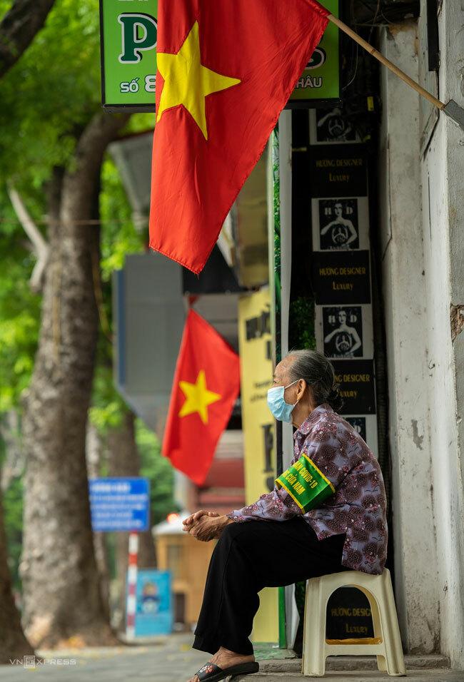 Cụ bà ngồi bảo vệ vùng xanh trước một ngõ trên phố Cửa Nam, Hà Nội, ngày 2/9/2021. Ảnh: Phạm Chiểu