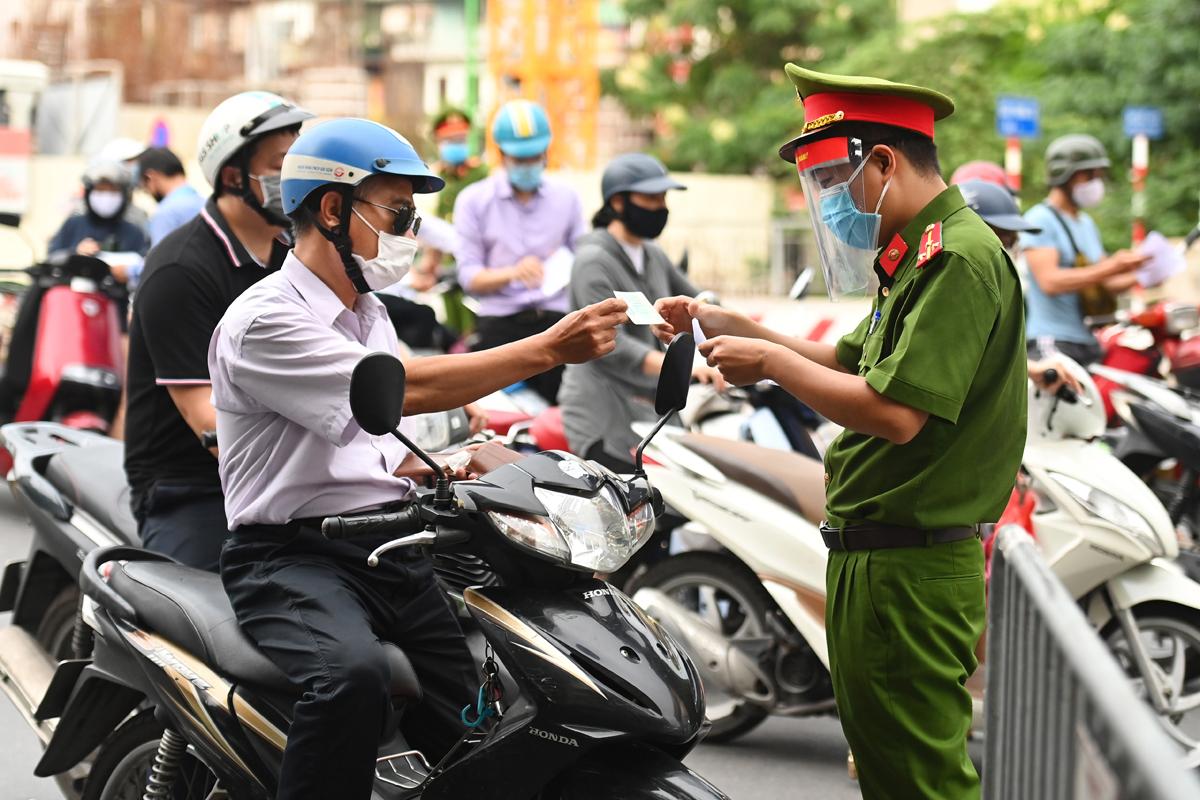 Lực lượng công an kiểm tra giấy điều kiện lưu thông của người tham gia giao thông tại phố Phạm Ngọc Thạch, ngày 28/7. Ảnh: Giang Huy.