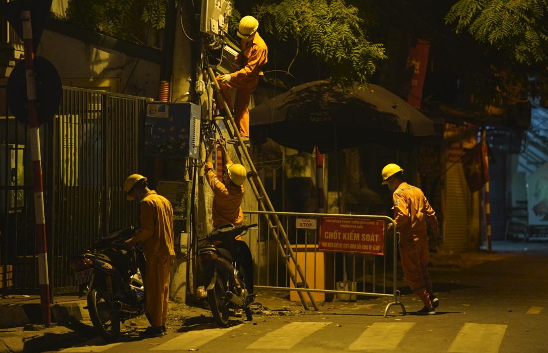 Công nhân nối đường dây điện cho chốt kiểm soát ở đường Hồ Tùng Mậu. Ảnh: Phạm Chiểu