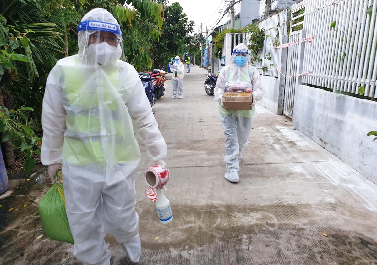 Nhân viên trạm y tế lưu động xã Tân Nhựt mang thuốc, lương thực hỗ trợ F0 điều trị tại nhà. Ảnh: An Phương