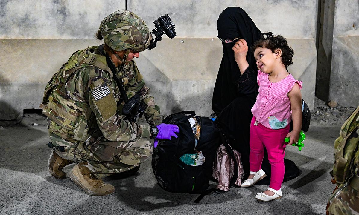Binh sĩ Mỹ kiểm tra hành lý của hai mẹ con Afghanistan tại sân bay Hamid Karzai ở thủ đô Kabul ngày 22/8. Ảnh: USCENTCOM.