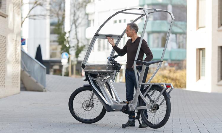 Tom Eisner kéo tấm màng plastic của nguyên mẫu xe đạp điện mới. Ảnh: AllWeatherBike
