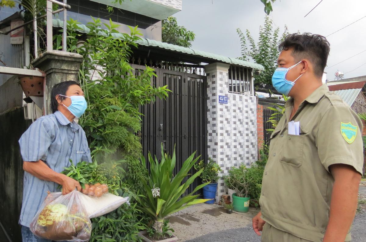 Anh Huỳnh Văn Hải phát thực phẩm cho người dân ở trọ trong tổ, ngày 2/9. Ảnh: Lê Tuyết